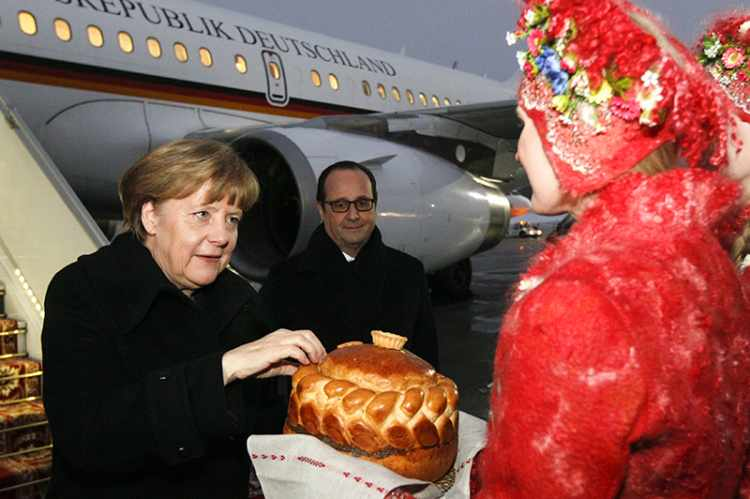 Germany's Chancellor Angela Merkel and France's President Francois Hollande take part in a welcoming ceremony after their meeting inside a plane at an airport near Minsk