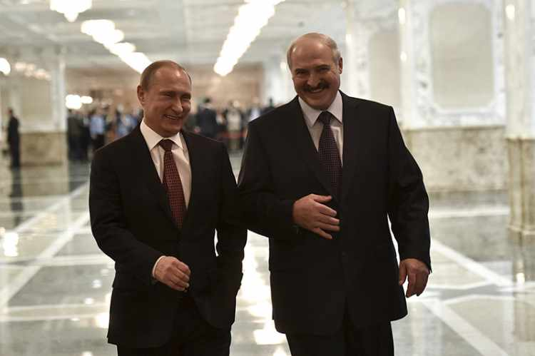 Vladimir Putin and Alexander Lukashenko laugh while walking before a meeting on resolving the Ukrainian crisis in Minsk