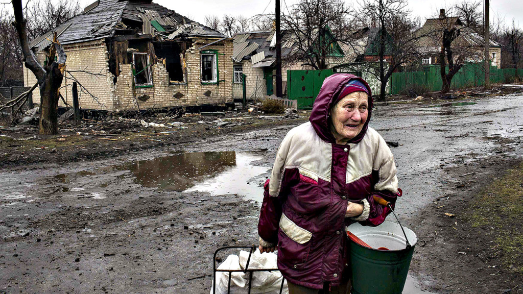 A woman cries as she walks past destroyed houses in the town of